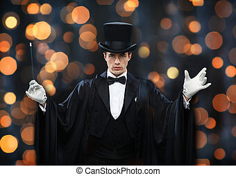 magician in top hat showing trick with magic wand -...