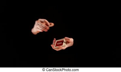 Magician makes trick with playing cards on black background