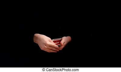 Magician making trick with playing cards on black background...