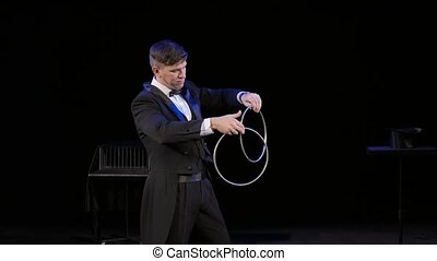 Magician manipulates iron hoops on thestage - Magician...