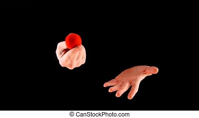 Magician performing with red ball on black background