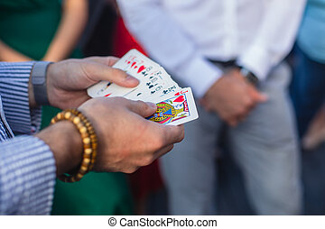 Magician showing card tricks focus in front of guests on party event wedding celebration, juggler performing show