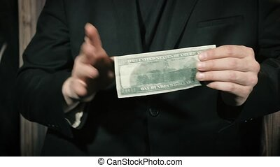 Magician shows a performance with a dollar bill