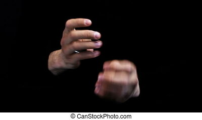 magician shows coin trick on black background
