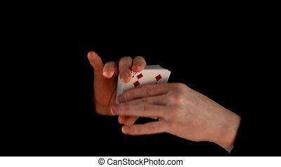 Magician shows playing card trick concept on black...
