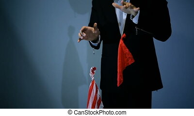 magician shows trick with flying red napkin on black background.