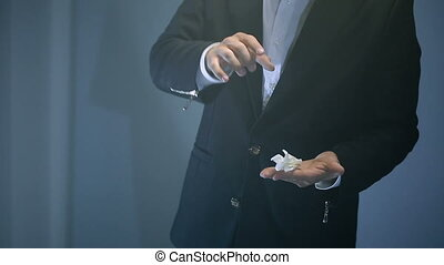 magician shows trick with flying white napkin on black background.