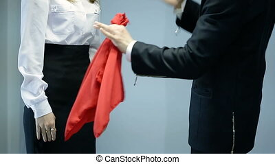 magician shows trick with red scarf and woman on dark background