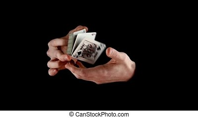 Magician shuffling the cards, on black, slow motion -...