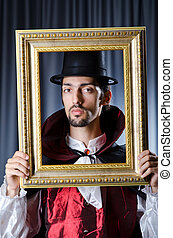 Magician with photoframe in studio