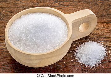 Magnesium sulfate (Epsom salts) in a rustic wooden scoop - ...