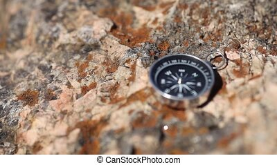 Magnetic compass with a black dial on a wild stone covered...
