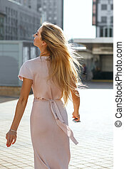 Magnificent blonde blue eyed model with flying hair wearing pink dress posing in sun glare