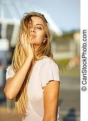 Magnificent blonde model with long hair posing at the background of street in sun light