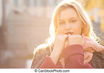 Magnificent blonde model with red lips wearing knitted scarf and coat, posing in rays of sun. Empty space
