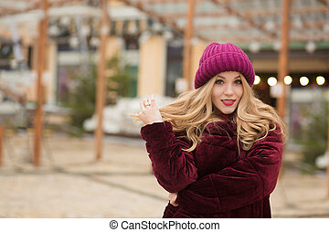 Magnificent blonde woman with long hair posing at the street in in Kyiv