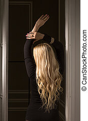 Magnificent blonde woman with long wavy hair posing at studio