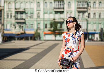 Magnificent brunette girl wearing trendy dress and glasses, posing at the street. Space for text