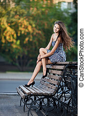 Magnificent brunette sits on bench which is on city street