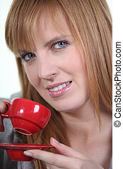 magnificent ginger woman drinking cup of coffee