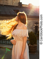 Magnificent ginger young model with naked long wavy hair in motion posing in sun glare