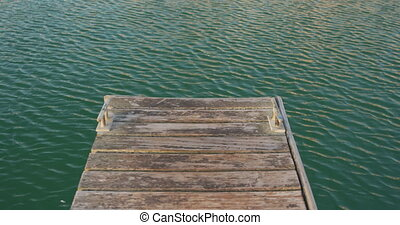 Magnificent view of an end of a jetty and small waves on a calm sea water, on a sunny day, in slow motion