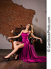 Magnificent young woman in luxurious dress is sitting in a chair in a luxury apartment. Classic vintage interior.