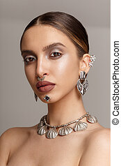 Cheerful female model, with silver jewelery, looking with attitude at camera, over grey background.