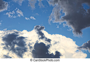 Magnificient white and grey cloudscape on blue sky.