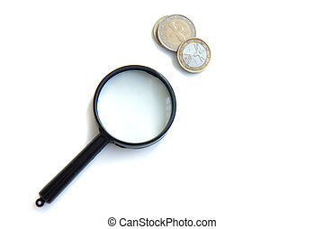 Magnifier and stack of coins isolated on white background