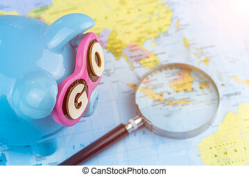 Magnifier laying on the defocused map. Saving piggy bank is ready for travel. GO slogan on sunglasses.