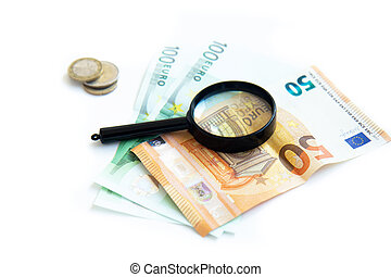 Magnifier, paper money and a stack of coins isolated on white background