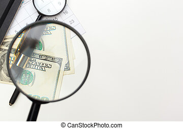 Magnifying glass and a pile of money.