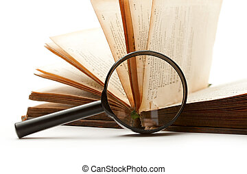 Magnifying glass and book isolated on white