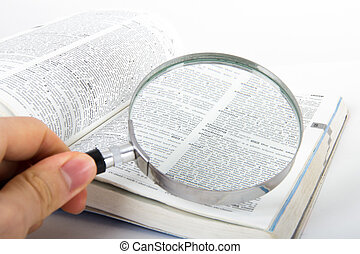 Magnifying Glass and Dictionary - Hand holding classic style...