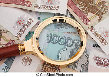 Magnifying glass and russian money. Crisis concept.