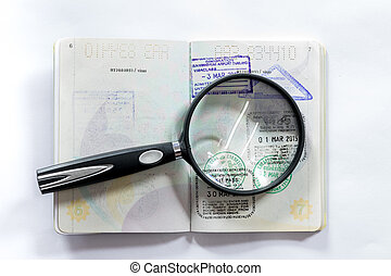 Magnifying glass and seals of various countries on the passport.