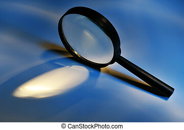 Magnifying glass - Conceptual magnifying glass on blue ...
