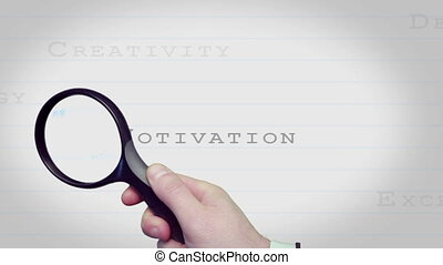 Magnifying glass finding motivating business words on lined...