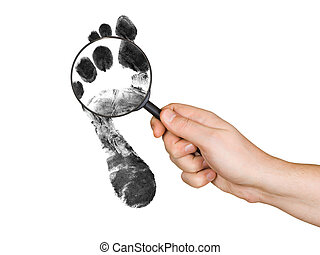 Magnifying glass in hand and foot printout