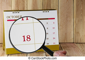 Magnifying glass in hand on calendar you can look Eighteenth date of month,Focus number Eighteen in October.