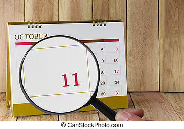 Magnifying glass in hand on calendar you can look Eleventh date of month,Focus number eleven in October.