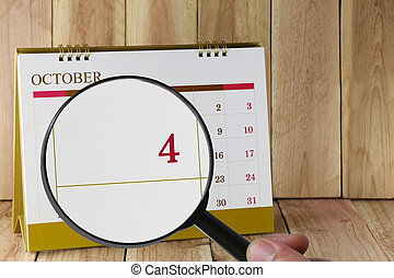 Magnifying glass in hand on calendar you can look Fourth...