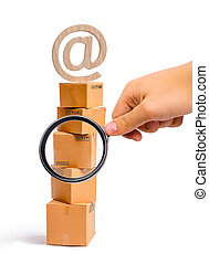 Magnifying glass is looking at the tower of cardboard boxes and an email symbol on top. concept of online sales, shopping and online shopping. Realization of goods and services through the Internet.