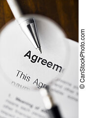 magnifying glass - Magnifying glass over agreement paperwork...