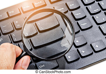 Magnifying glass on a computer keyboard.