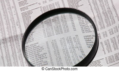 Magnifying glass showing numbers from a newspaper