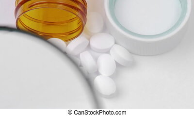 Magnifying glass showing white pills