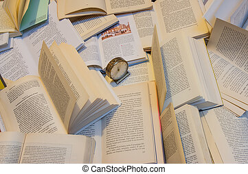 magnifying glass, some books and a clock upper a table