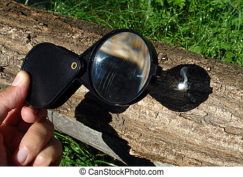 Magnifying glass starting fire - Sunlight focused by a...